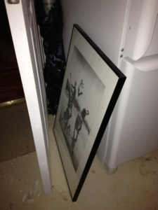 My print sandwiched between the basement door and our old fridge. Nobody puts baby in the corner.